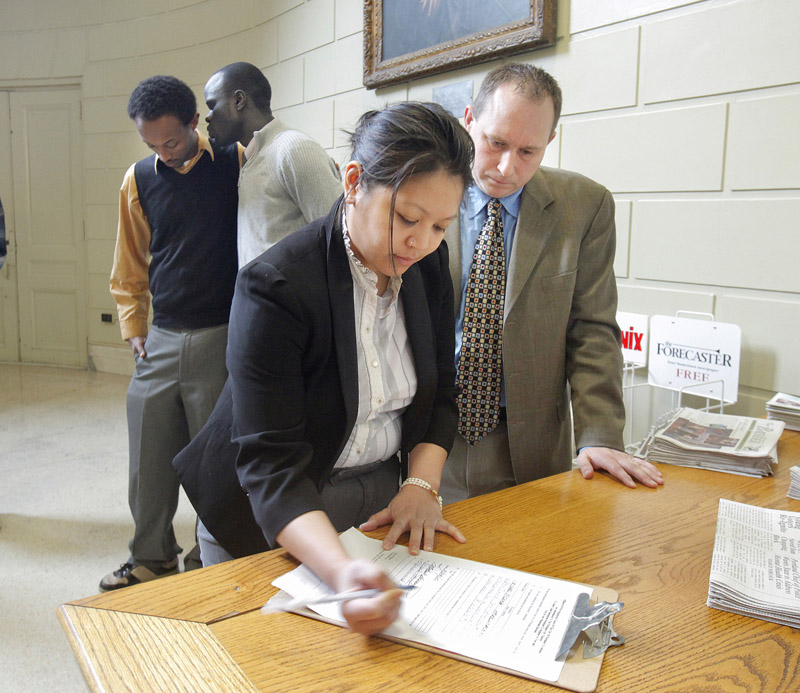 Will Everitt watches as Jenna Vendil signs an affidavit today to initiate a petition drive looking to give non-citizens the right to vote in city elections. In the background are two other members of the committee initiating the petition, Mohammed Dini, left, and Alfred Jacob. The group needs to gather 4,500 signatures to put the referendum on the November ballot.