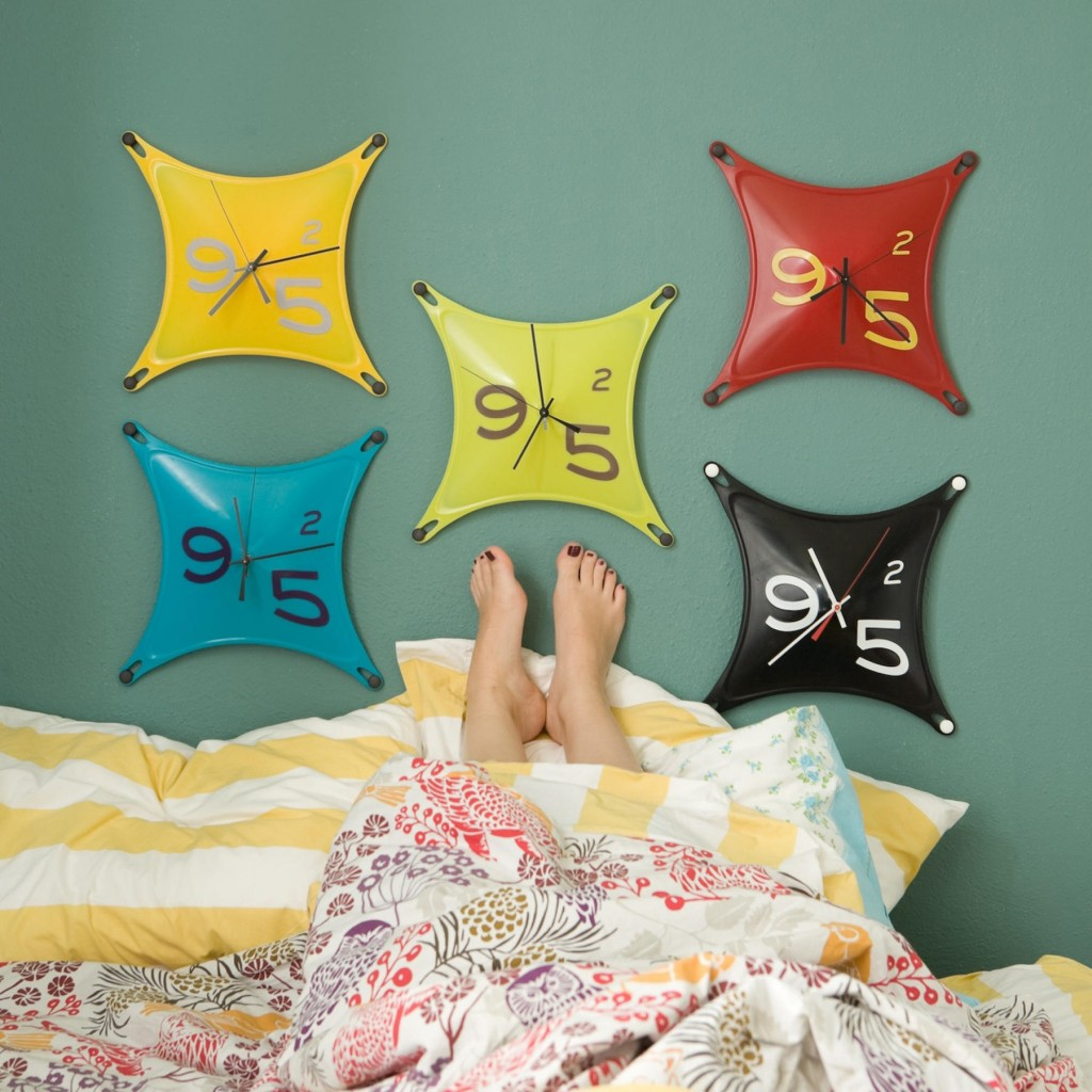 Stretch clocks made of silicone, created by SCAD graduate Charles Heidlinger, grace a wall.