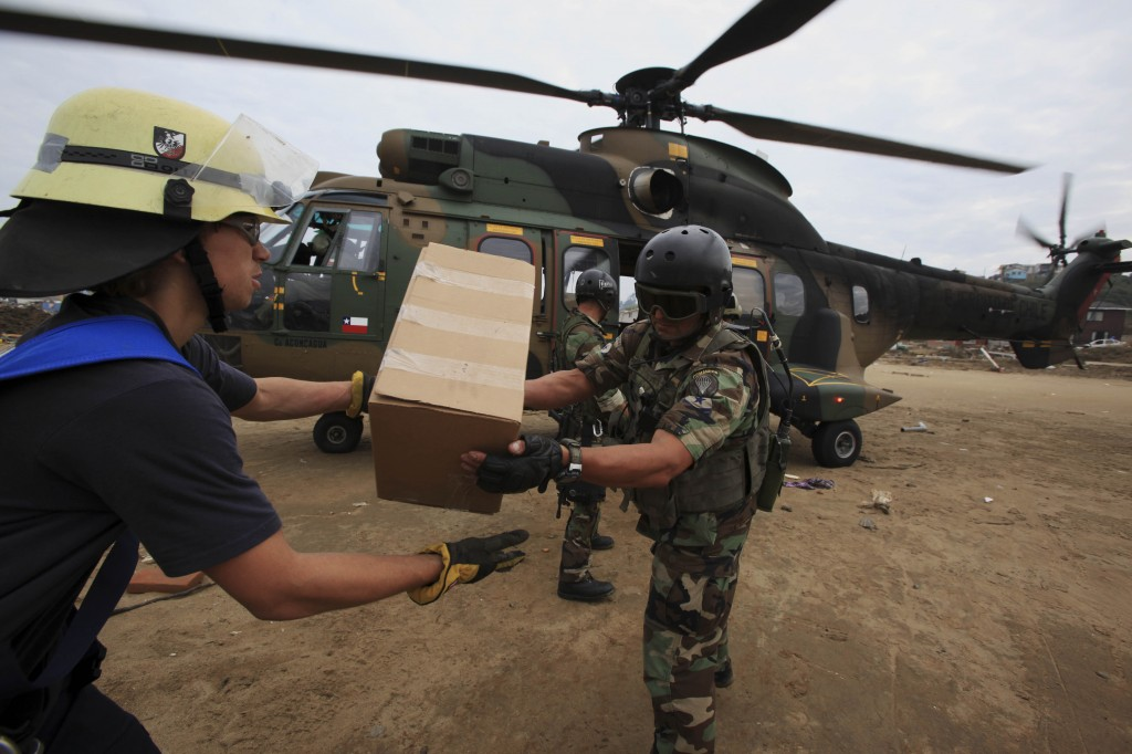 Troops and firefighters unload relief supplies from a military helicopter Wednesday in Dichato, Chile. The government deployed thousands of troops throughout the country's central coastal region to curb looting and facilitate aid distribution.
