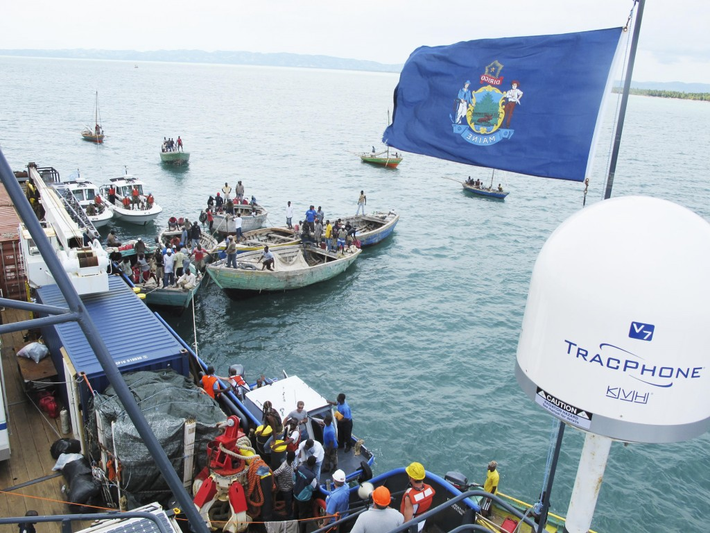 """A small fleet of Haitian boats, monitored by two United Nations patrol boats, makes it way alongside Sea Hunter as offloading operations get under way Friday. """"This is what we started out in Portland for,"""" said Sea Hunter's owner, Greg Brooks."""