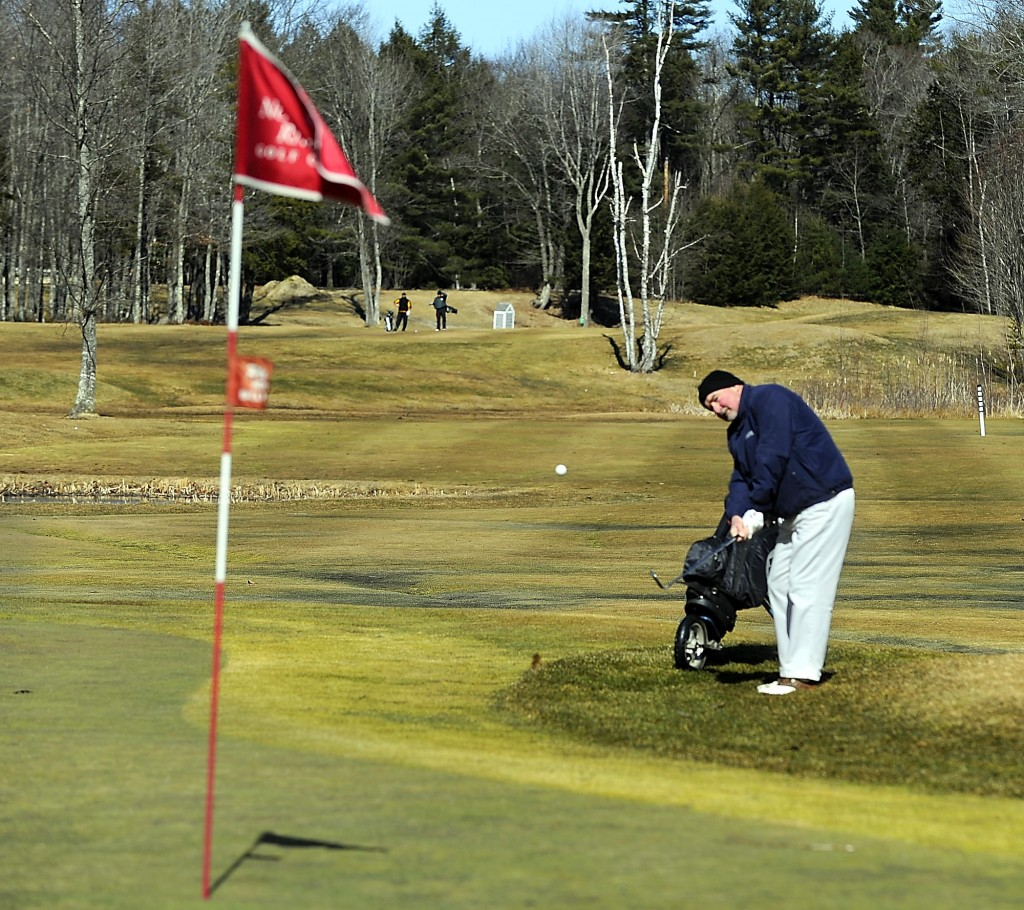 Peter Allen of Portland chips to the green on the third hole of Nonesuch Golf Course in Scarborough on Friday. Warm weather has encouraged many golfers to start the season early, and tee times are sold out today at Nonesuch, says Dan Hourihan, owner and manager. It's just one of the signs that this hasn't been a typical Maine winter.