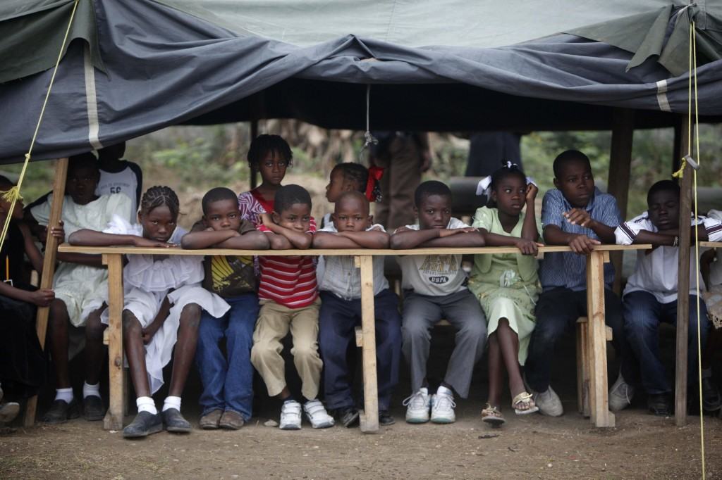 Children wait for the inauguration of a school that will be run by an Israeli group at a camp for earthquake survivors inPort-au-Prince on Friday. Donations from around the world have poured into Haiti since the January disaster.