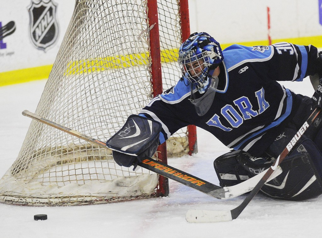 York goalie Alex Ahrikenchikh reaches with his stick for the puck Saturday during the 3-1 loss to Brewer in the Class B state championship game at Lewiston. Ahrikenchikh made 19 saves.