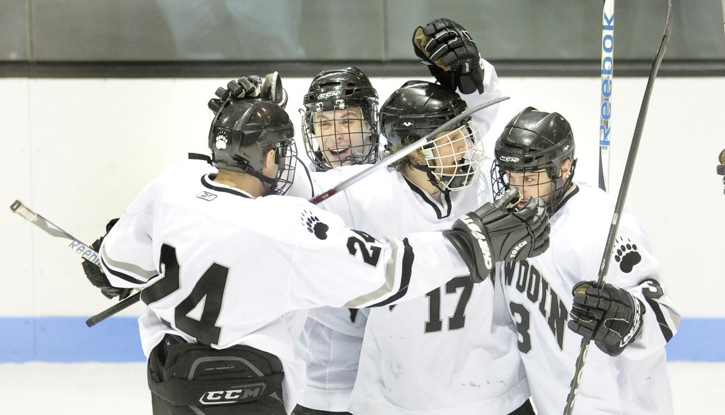 Leland Fidler (17) celebrates with his teammates after scoring one of Bowdoin's five third-period goals against Hamilton.