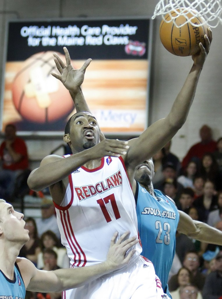 Darnell Lazare of the Red Claws slides between Greg Stiemsma, left, and Raymond Sykes of Sioux Falls for a layup Sunday night during the Skyforce's 99-98 victory at the Portland Expo.