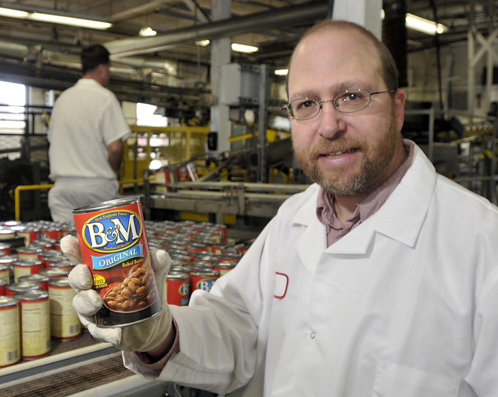 Ray Routhier holds a can of B&M Baked Beans, ready for the stores. B&M employees take pride in the fact that their product is baked, noting that some rivals just steam their beans.