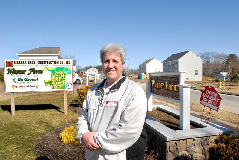 "Bill Risbara stands in front of a Risbara Bros. construction site in Gorham where he is developing a 42-lot subdivision. Risbara said he''s down to 16 lots at Wagner Farm and is preparing to buy more land. """"We''re in an acquisition mode,"""" he said."