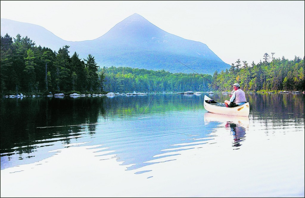 A fisherman tries his luck on Rocky Pond, with Doubletop Mountain in the background and reflected in the water. In the northern half of Maine, the fishing season will remain the same in order to protect the prized native brook trout fisheries there.