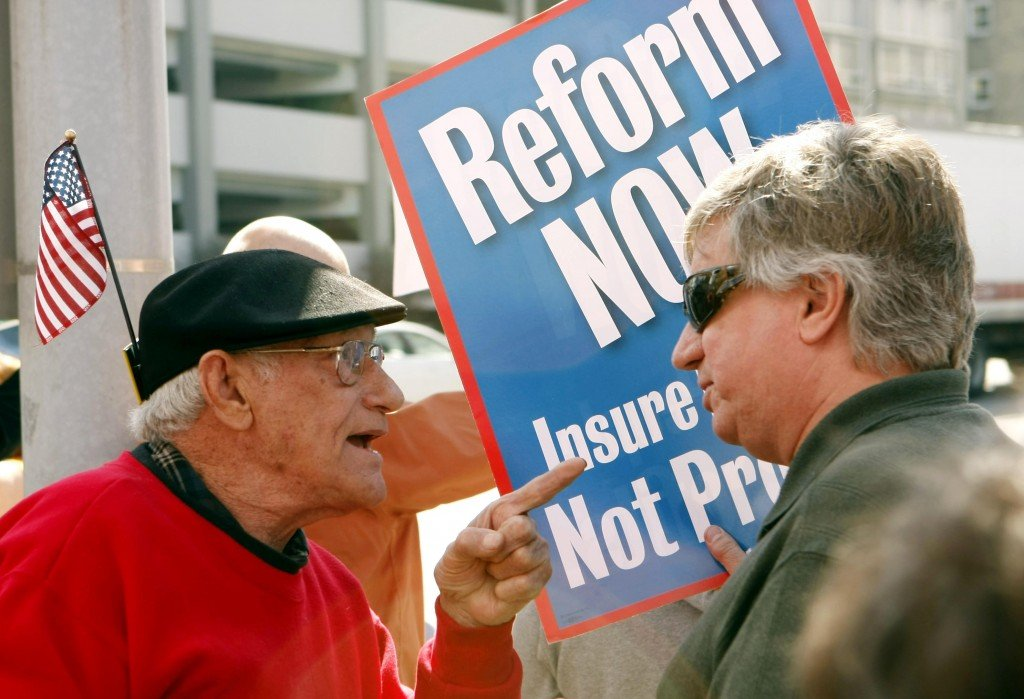 George Martin, left, and Walt Stoelting argue over health care reform during a rally Thursday outside the district office of Rep. Joe Donnelly in South Bend, Ind. Groups on both sides of the debate are keeping pressure on three Indiana Democratic congressmen, including Donnelly, who say they haven't decided how they'll vote.