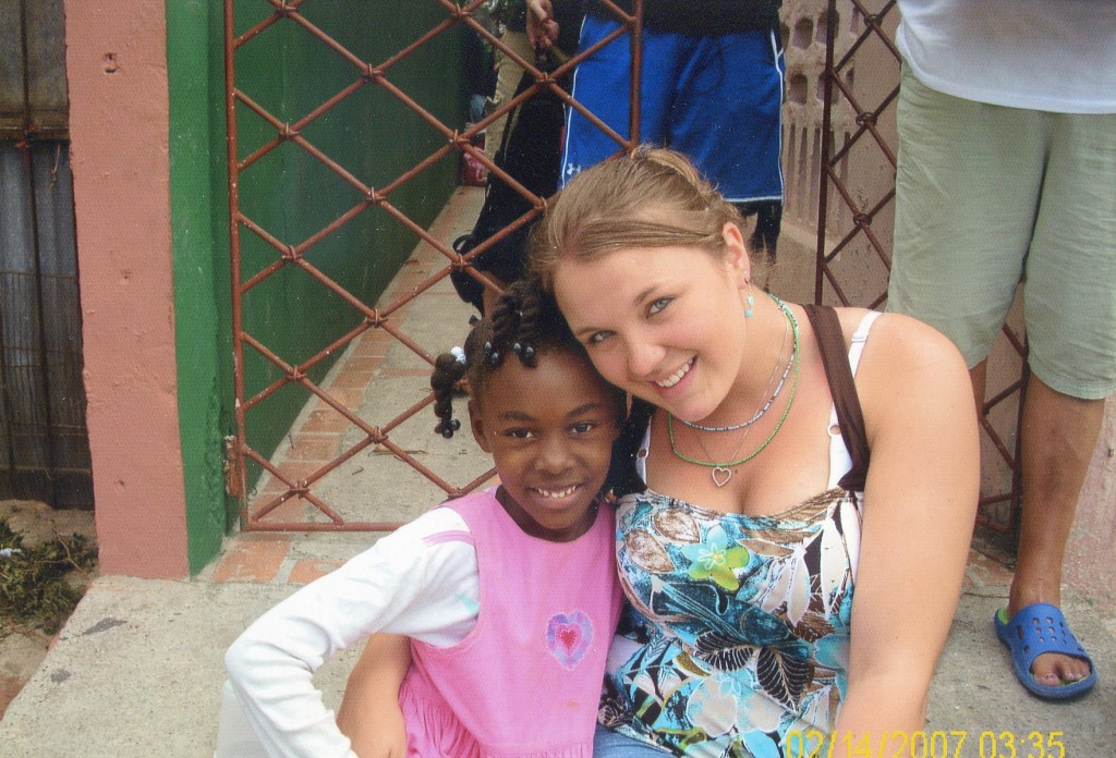 Courtney Connolly, a former dropout who is a senior at Portland High School, poses with a child she met while helping Seeds of Independence provide health care to sugar cane workers in the Dominican Republic last year. Connolly will return to the Caribbean country next week for a second stint with the Freeport nonprofit that helps at-risk teenagers.