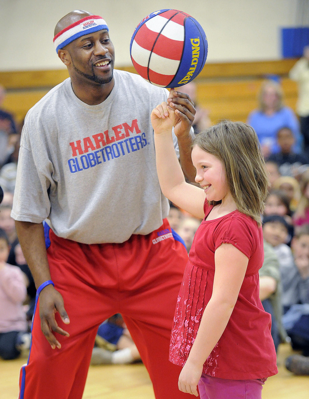 On a visit last Friday to Reiche Elementary, Hot Shot Branch of the Globetrotters gives Malea Cross-Robertson a lesson on the old spinning ball routine.