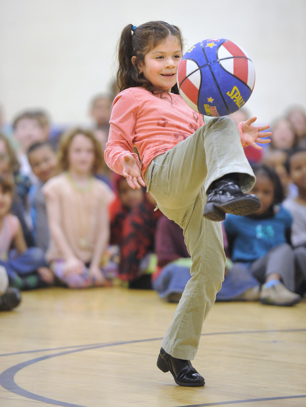 Reiche first-grader Ingrid Rosales demonstrates another trick Branch taught students in last Friday's visit, bouncing the ball off her knee to a teammate.