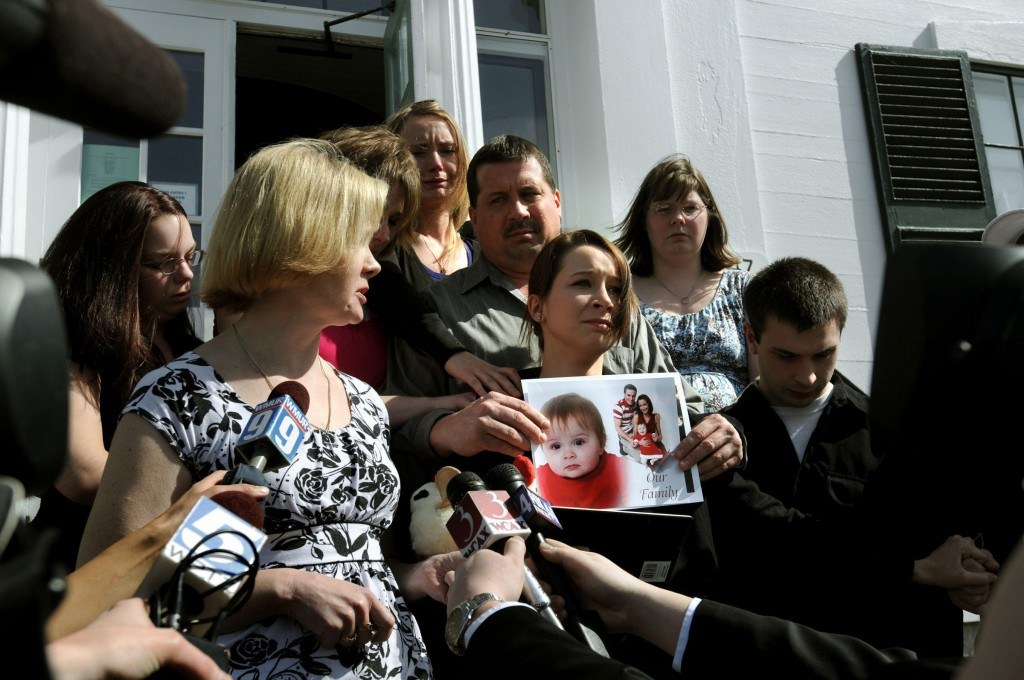 Janine McDaniel, left, of Andover, N.H., speaks outside of court Friday about the death of her granddaughter, one-year-old Kyleigh McDaniel. Kyleigh's mother, MacKenzie McDaniel, also of Andover, N.H., holds photographs of her daughter.