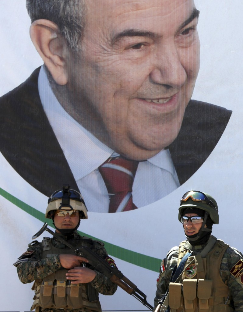 Iraqi policemen stand guard in front of an election campaign poster for former Iraqi Prime Minister Ayad Allawi at a checkpoint in Baghdad, Iraq, on Saturday.