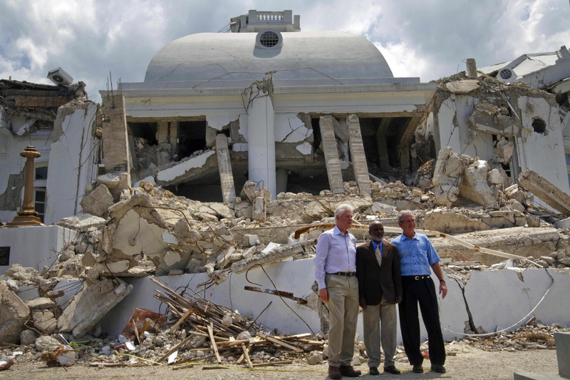 Haitian President Rene Preval, center, former President George W. Bush, right, and former President and U.N. special envoy for Haiti Bill Clinton pose Monday in front of the earthquake damaged national palace in Port-au-Prince.