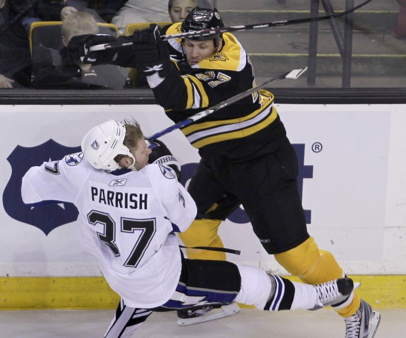Steve Begin of the Bruins checks Tampa Bay's Mark Parrish during Thursday's game in Boston. The Bruins lost 5-3 despite outshooting the Lightning 50-18.