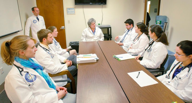 Elisabeth DelPrete, D.O., center, chair of the University of New England's department of family medicine, meets last week with first-year medical students to discuss the mock physicals in which they had just participated. Fifteen percent of Maine's primary care doctors are UNE graduates with a doctor of osteopathy degree, said the medical school's dean.