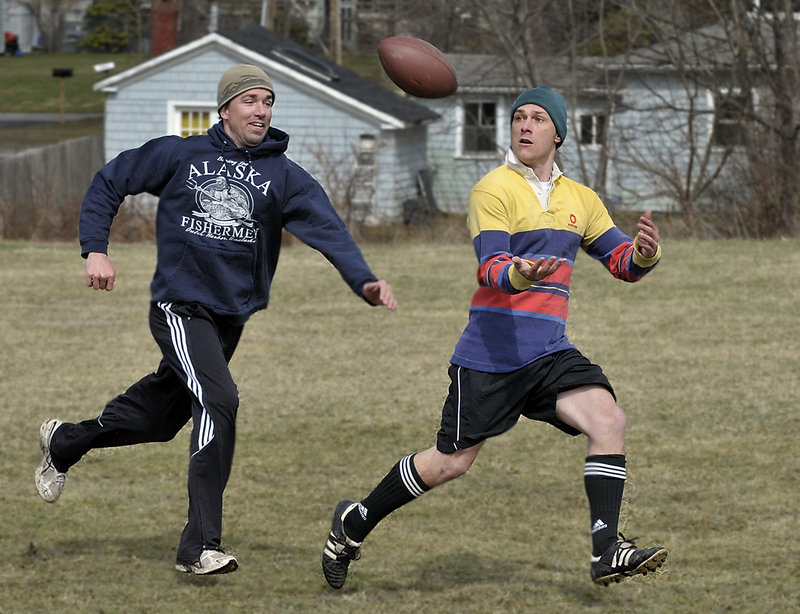 Mike McCoy, right, prepares to make a reception for a touchdown with Shannon Carroll in pursuit as they and other law students from the University of Southern Maine play their weekly football game in Payson Park in Portland. Carroll said he and seven friends have been playing at the park every Friday since February, rain or shine.