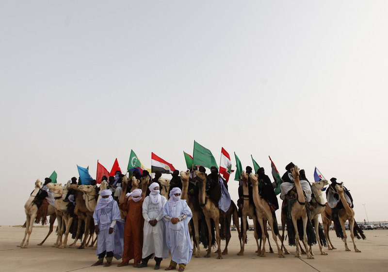 Libyan camel riders holding flags of Arab countries gather as Arab League leaders arrive for the summit in Sirte, Libya.