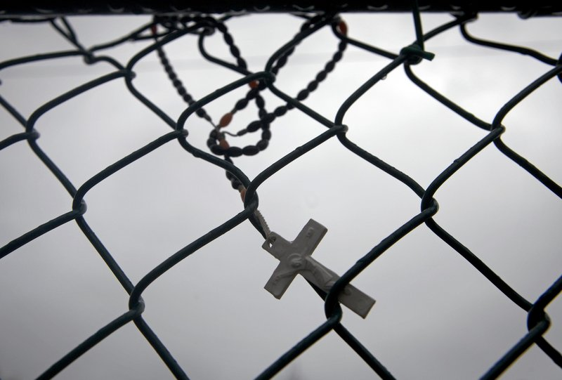 A cross hangs on a fence near the train station in Patchogue, N.Y., where Ecuadorean immigrant Marcelo Lucero was killed in a hate crime in 2008.