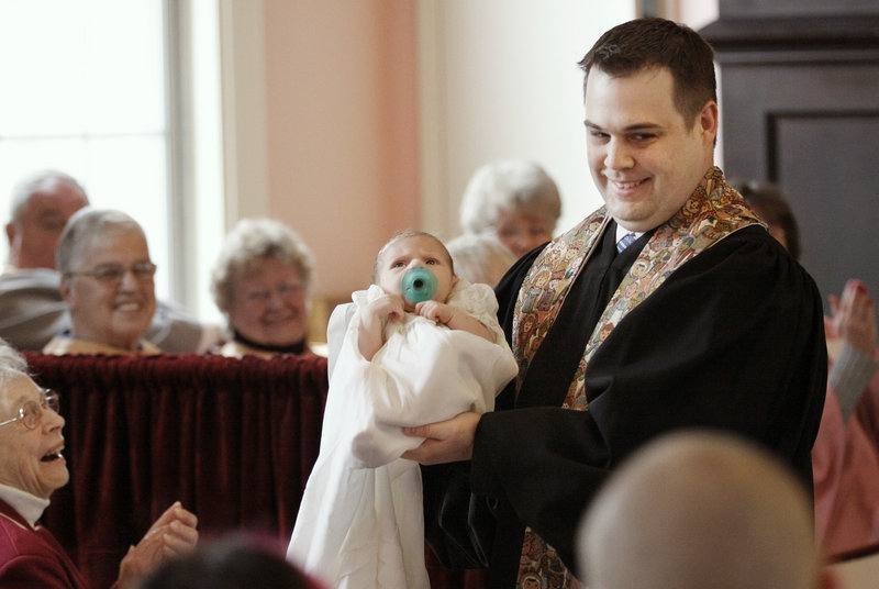 The Rev. Derek White shows his 6-week-old son, Silas, to the congregation after baptizing him at the First Congregational Church in Kennebunkport on Palm Sunday.