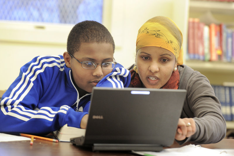 Nadar Mohamud, right, an AmeriCorps volunteer who grew up in the Kennedy Park neighborhood, helps Portland High School freshman Abdi Mohamed work on a report he is writing about Acadia National Park at Kennedy Park's study center.