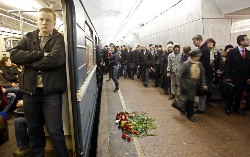 Commuters walk past flowers on the platform at the Lubyanka subway station in Moscow, which was hit by one of two explosions during rush hour on Monday.