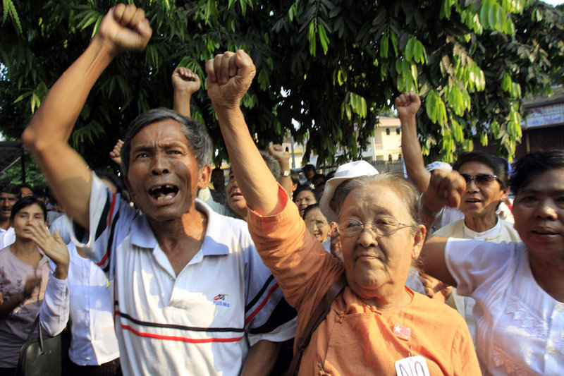 Members of detained pro-democracy leader Aung San Suu Kyi's National League for Democracy Party chant slogans demanding her release in a rally outside the party's headquarters Monday in Yangon, Myanmar.
