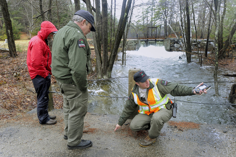 Forest Ranger Matt Bennett, right, explains the flooded road conditions ahead to his supervisor, Gregg Hesslien, while monitoring the outlet dam on Bickford Pond in Porter. A collapsed dam prompted emergency officials to close nearby Colcord Pond Road.