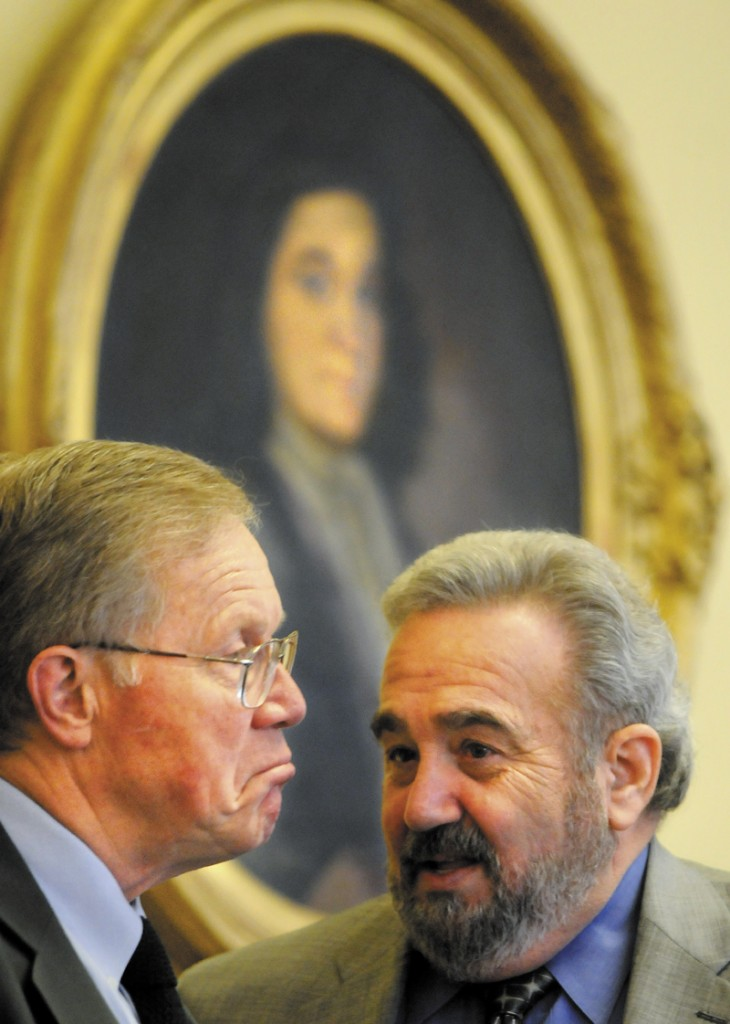 Maine Sens. Richard Nass, R-Acton, and Stanley Gerzofsky, D-Brunswick, confer beneath a portrait of William Phips in the Maine Senate on Tuesday. The Legislature completed work on a supplemental budget that closes a $310 million shortfall and took hundreds of hours to craft.