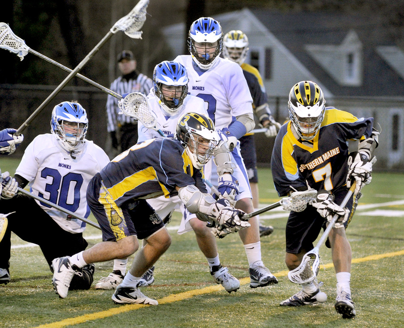 Mark White, right, and Kayle Hamilton of the University of Southern Maine scramble for a loose ball in front of St. Joseph's goalie Christopher Driscoll, 30, during Wednesday night's men's lacrosse game at Deering High. White and Hamilton each had three goals in USM's 18-5 victory.