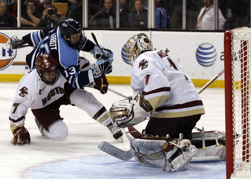 Boston College goalie John Muse stands his ground Saturday night as Spencer Abbott of the University of Maine is upended by Carl Sneep. Boston College won in overtime.