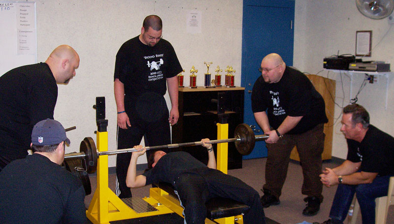 From left, Chris Bisson, seated, as a judge; spotters Erik Moody, Chris Chudzik and Don Young; Del Sargent, seated, as a judge. The lifter is Rebecca Miller.