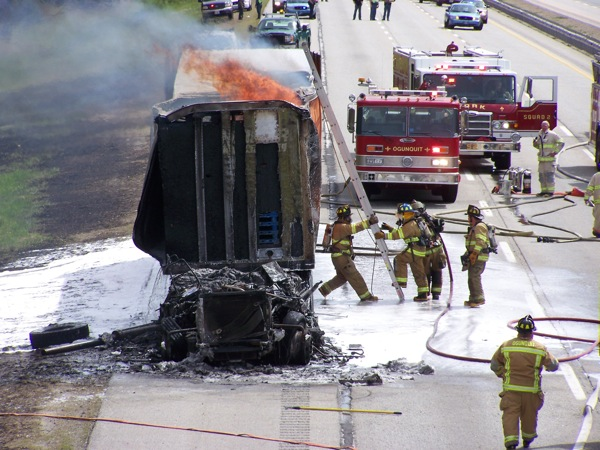 Firefighters work to extinguish the flames that consumed the cab of the tractor-trailer truck.