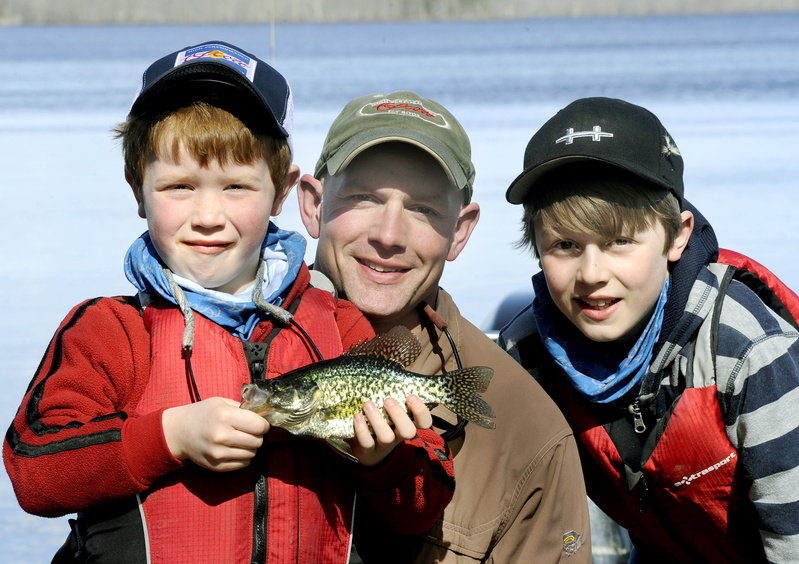 Kevin McKay, center, has taught his sons, Jax, 7, left, and Tait, 10, to fly fish. Jax holds a black crappie caught at Hermon Pond.