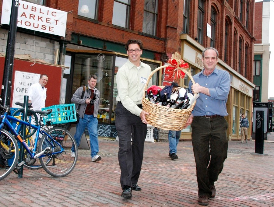 Paul Drinan, left, media coordinator, and store owner Bill Milliken carry a basket of assorted Maine microbrews, along with assorted other Maine products from the Portland Market House, out to a car at Monument Square where it will begin it's journey to President Obama Monday, April 19, 2010. (Jill Brady/Staff Photographer)