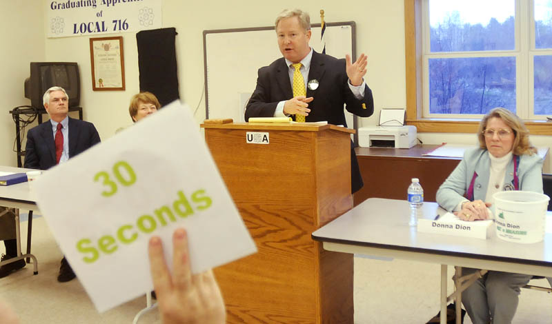 DEMOCRATS' DISCUSSION: Pat McGowan is warned with a sign that he has 30 seconds to finish speaking Thursday evening during a forum for Democratic candidates for governor held at Local 716, Plumbers and Pipefitters Union, in Augusta. Steven Rowe, left, Elizabeth Mitchell, and write-in candidate Donna Dion, right, attended the event.