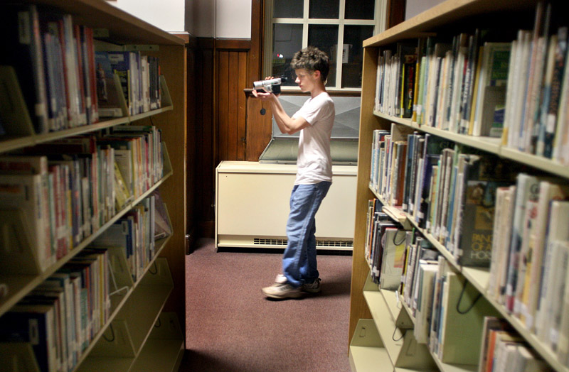 PATHS new media student Dylan Sargent, 18, films Kara Marston as she asks questions hoping to hear a response from paranormal activity in the library at Portland High School on Wednesday.