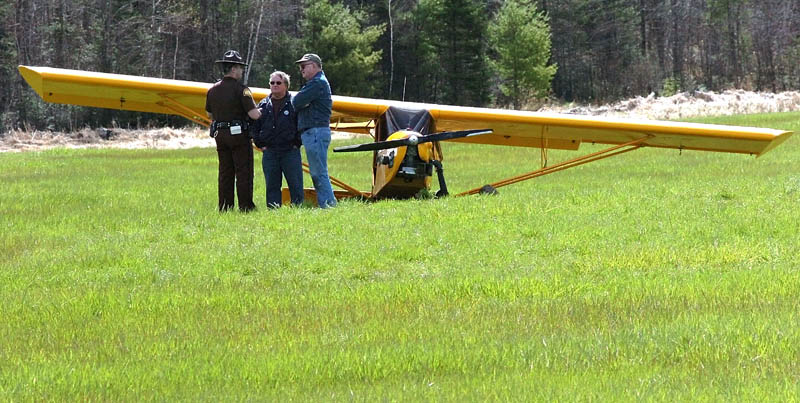 DOWN: Pilot Alton Carter, right, of Industry, speaks with Somerset Deputy Ritchie Putnam beside Carter's airplane, which crashed Tuesday in a wet field off Elm Street in Mercer. At center is Donald Carr, whom Carter called to tell that he had crashed. There were no injuries, and the FAA is investigating the incident.