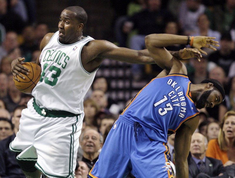 Kendrick Perkins of the Boston Celtics holds the ball with one hand and holds off James Harden with the other for a rebound Wednesday night. Oklahoma City won, 109-104.