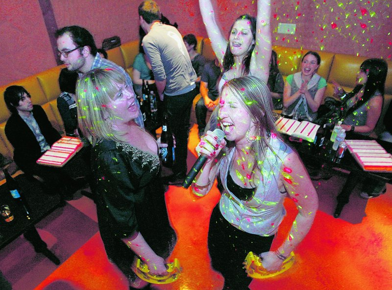 Anne Walls and Samatha Hackett, left, sing karaoke with friends at Walls' birthday party at Rosen Music Studio, a karaoke/bar/restaurant in Los Angeles, Calif., last month. Sales of karaoke machines have slumped since the karaoke industry peaked in 2002.