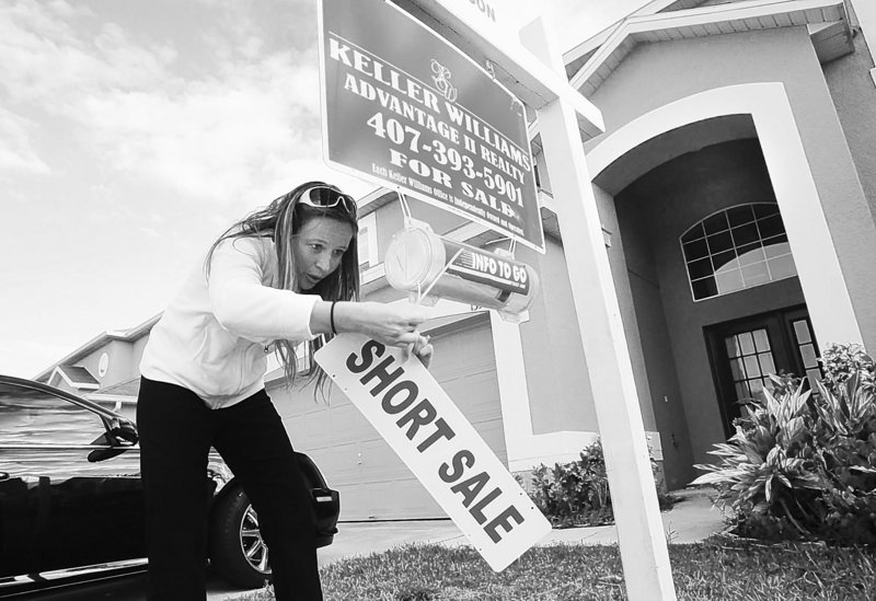 Mysty Stange puts up a short sale sign on a house in Orlando, Fla. Short sales made up 8 percent of the market in January, compared to 5 percent a year earlier.