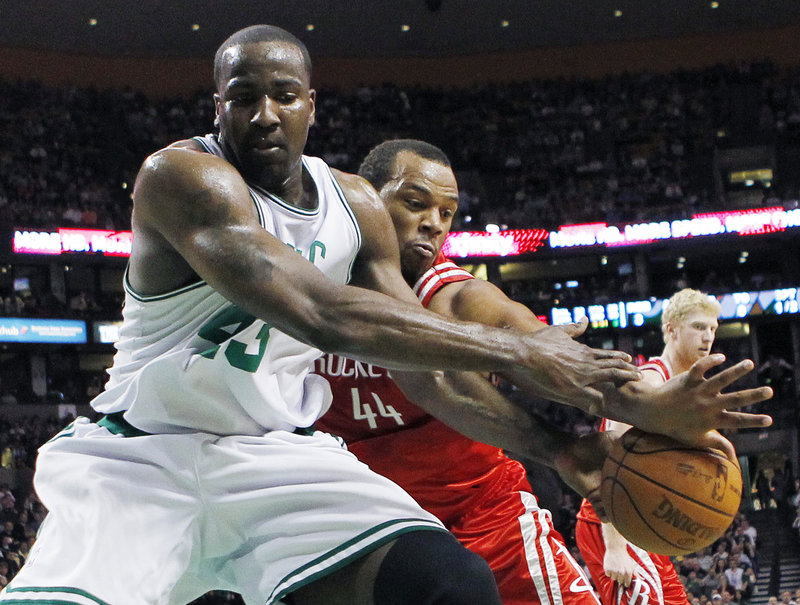 Kendrick Perkins of the Boston Celtics, left, competes with Chuck Hayes of the Houston Rockets for a loose ball Friday night in the first quarter of Houston's 119-114 overtime victory. Boston has lost three straight home games.