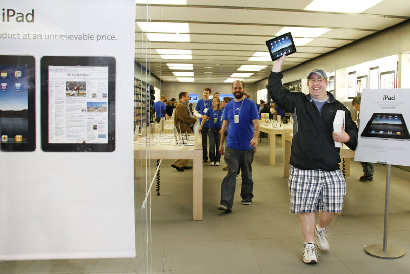 Dallas Cardinale of Maryland, who was visiting his mother who lives in Bridgton, holds up his new iPad, the first one sold Saturday at the Apple Store at the Maine Mall in South Portland.