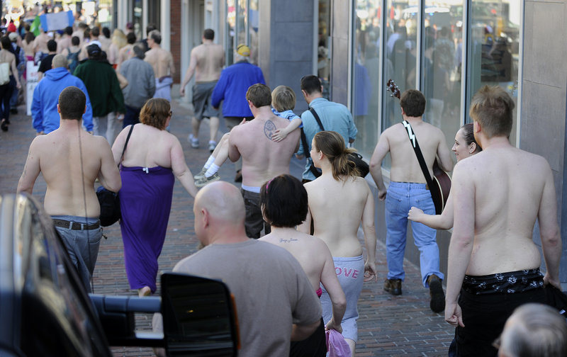 Bare-chested men and women walk together along a Congress Street sidewalk Saturday in Portland as part of an effort to promote equal opportunity public toplessness.