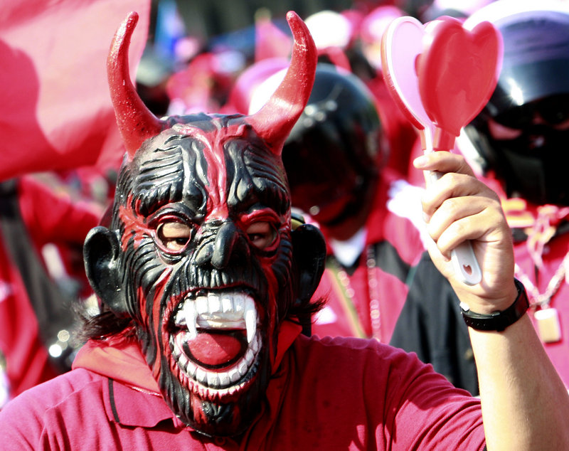 A supporter of ousted Prime Minister Thaksin Shinawatra wears a mask and waves a noisemaker during an anti-government demonstration in Bangkok, Thailand, on Saturday.