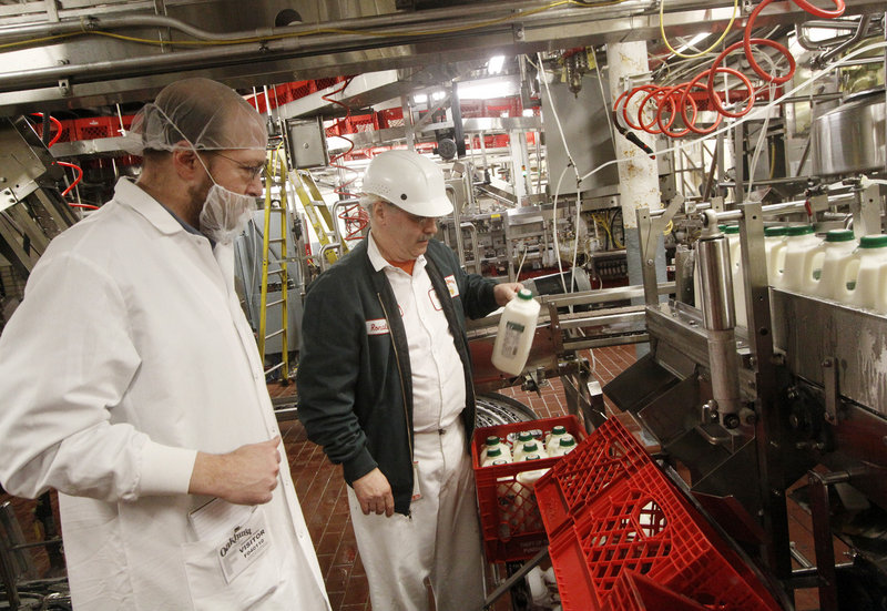Reporter Ray Routhier, left, works with Ronald Madore Jr. on the bottling line at Oakhurst Dairy in Portland. Madore, who's worked at Oakhurst for 40 years, runs quality checks every 15 minutes.
