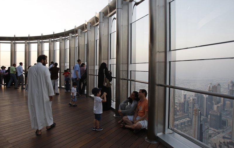 A boy takes a picture of his parents on the 124th-floor observation deck of the world's tallest skyscraper Sunday in Dubai. The deck was shut in February after an elevator malfunction.