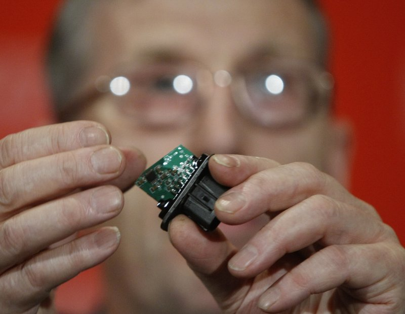 Anthony Anderson, an electrical failure expert, holds an electronic chip from a gas pedal assembly during a news conference March 23. Some groups say electronics could be the cause of sudden acceleration in Toyotas.