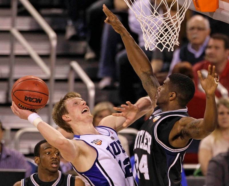 Kyle Singler, left, of Duke faces plenty of pressure from Butler's Avery Jukes as he tries to put up a shot Monday night in the men's final at Indianapolis. Singler had 19 points in the Blue Devils' 61-59 victory.